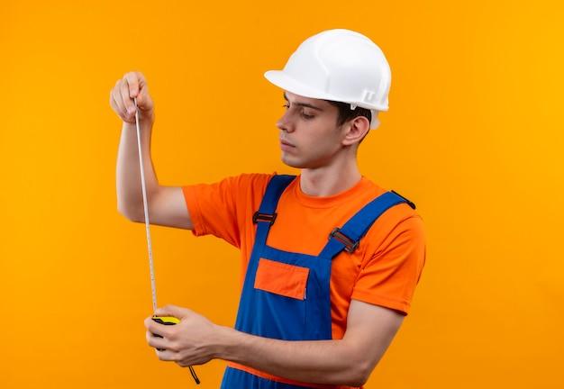 Junger baumeistermann, der bauuniform und sicherheitshelm trägt, der einen zähler für das messen hält