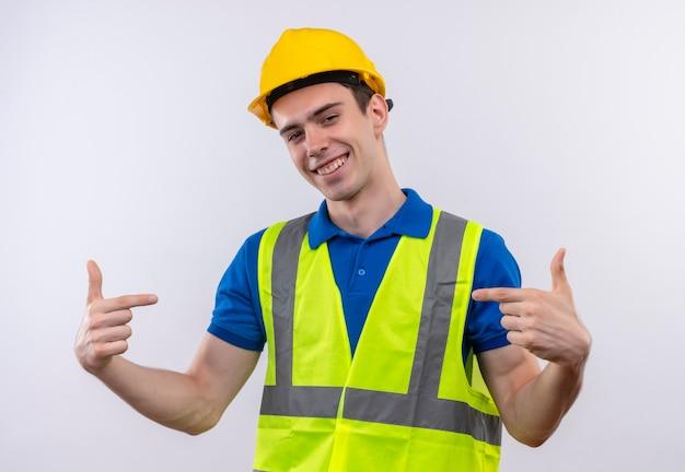 Junger baumeistermann, der bauuniform und sicherheitshelm trägt, der glücklich mit zeigefingern zeigt