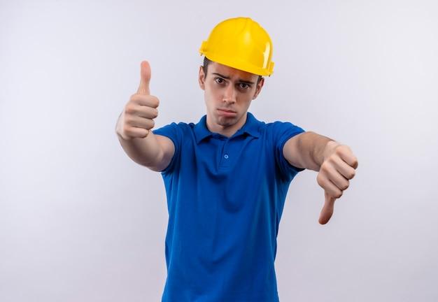 Junger baumeistermann, der bauuniform und sicherheitshelm trägt, der glückliche daumen hoch und unglückliche daumen unten tut