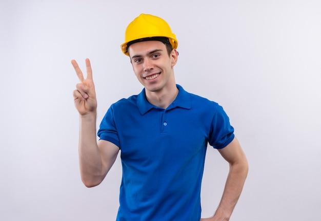 Junger baumeistermann, der bauuniform und sicherheitshelm trägt, der glücklichen frieden mit daumen tut