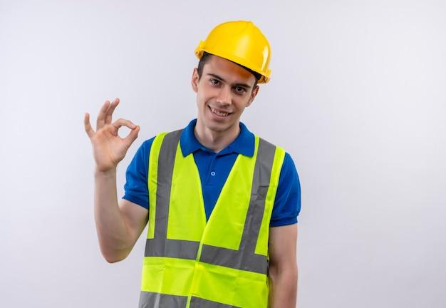 Junger baumeistermann, der bauuniform und sicherheitshelm trägt, der mit den fingern in ordnung tut