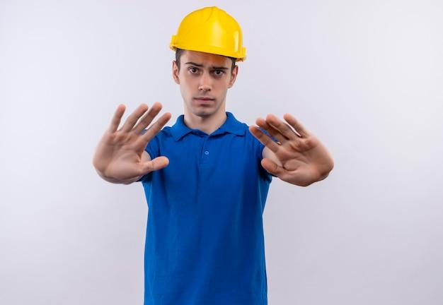Junger baumeistermann, der bauuniform und sicherheitshelm trägt, der stoppgeste mit händen tut
