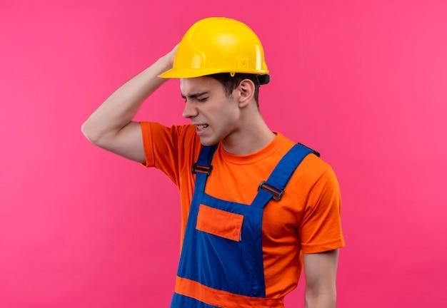 Junger baumeistermann, der bauuniform und sicherheitshelm trägt, der unter kopfschmerzen leidet, die seinen kopf mit der rechten hand von kopfschmerzen halten