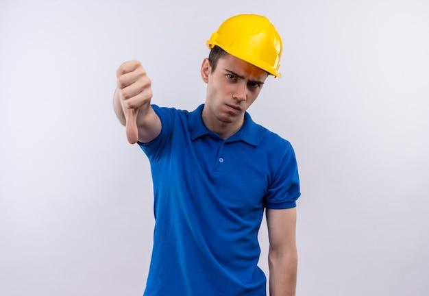 Junger baumeistermann, der bauuniform und sicherheitshelm trägt, der verärgerte daumen nach unten tut