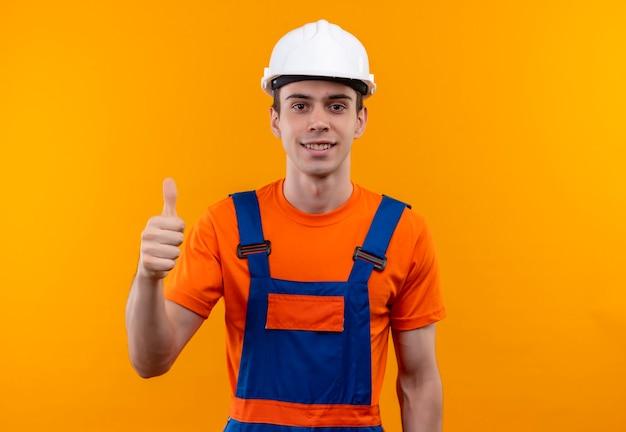 Junger baumeistermann, der bauuniform und sicherheitshelm trägt, die glückliche daumen hoch tun