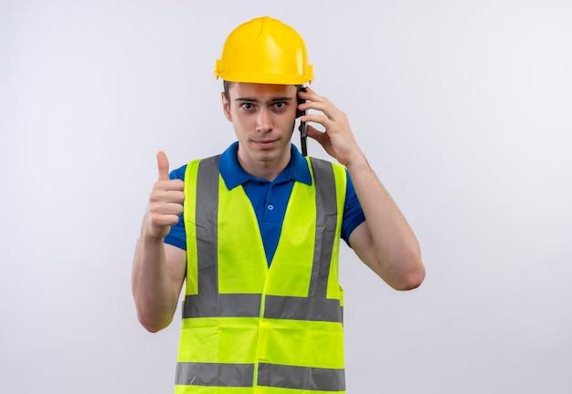 Junger baumeistermann, der bauuniform und sicherheitshelm trägt, die glückliche daumen hoch und am telefon sprechen