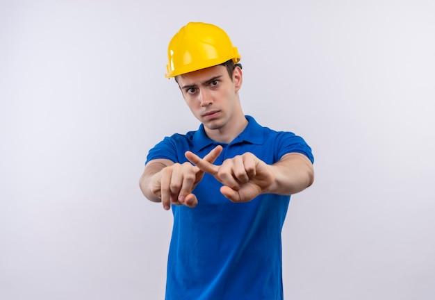 Junger baumeistermann, der bauuniform und sicherheitshelm trägt, kreuzt zeigefinger