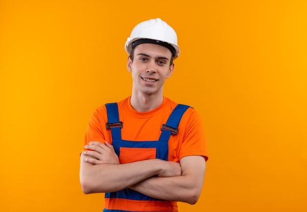 Junger baumeistermann, der bauuniform und sicherheitshelm trägt, lächelt