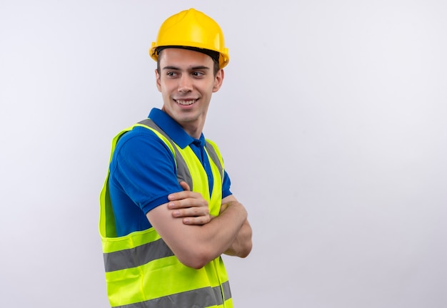 Junger baumeistermann, der bauuniform und sicherheitshelm trägt, schaut glücklich seitwärts