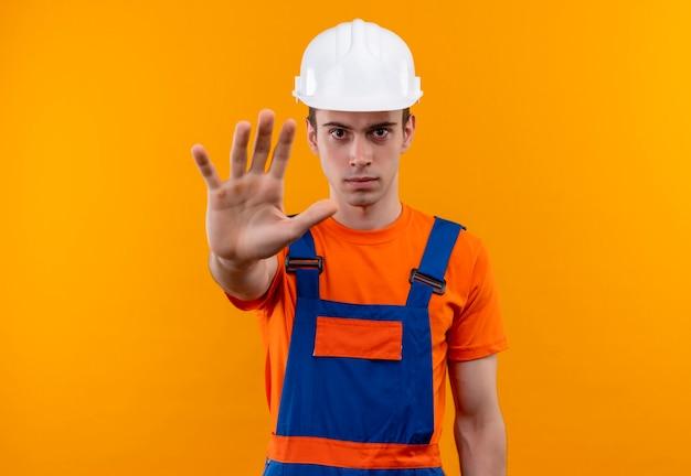 Junger baumeistermann, der bauuniform und sicherheitshelm trägt, stoppt mit der linken hand