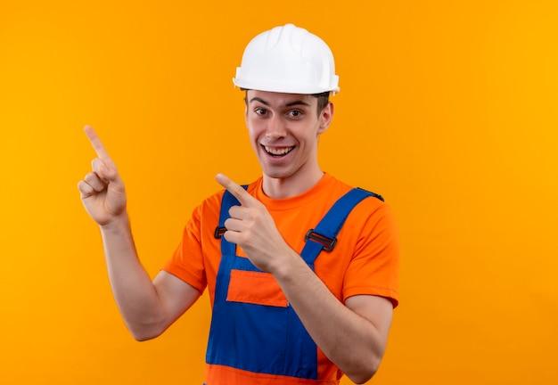 Junger baumeistermann, der bauuniform und sicherheitshelm trägt und mit den fingern nach oben zeigt