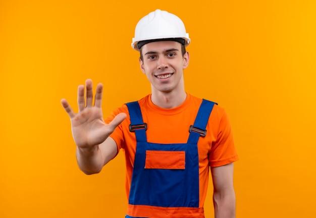 Junger baumeistermann, der bauuniform und sicherheitshelm trägt, zeigt fünf mit der linken hand