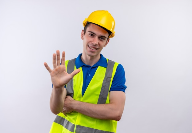 Junger baumeistermann, der bauuniform und sicherheitshelm trägt, zeigt glücklich fünf mit der hand