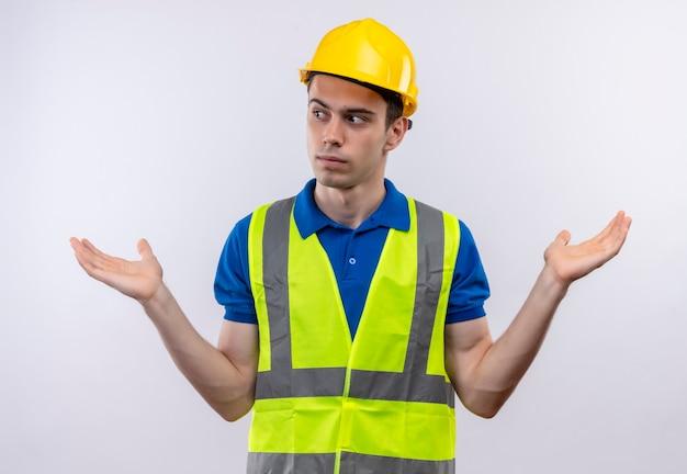 Junger baumeistermann, der bauuniform und sicherheitshelm verwirrt trägt