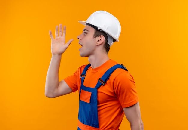 Junger baumeistermann, der bauuniform und sicherheitshelmanrufe trägt