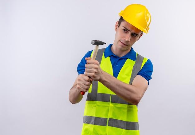 Junger baumeistermann, der bauuniform und sicherheitshelmhämmer trägt