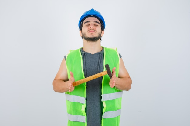 Junger baumeistermann, der hammer hält, während augen in arbeitskleidunguniform schließt und selbstbewusst, vorderansicht schaut.