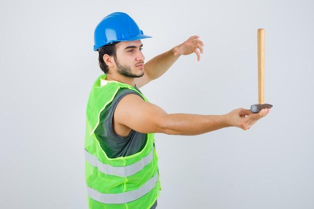 Junger baumeistermann, der hammer hält, während hand in arbeitskleidunguniform angehoben wird und vorsichtig schaut, vorderansicht.