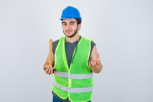 Junger baumeistermann, der hammer hält, während palme in arbeitskleidunguniform beiseite spreizend und fröhlich aussehend. vorderansicht.