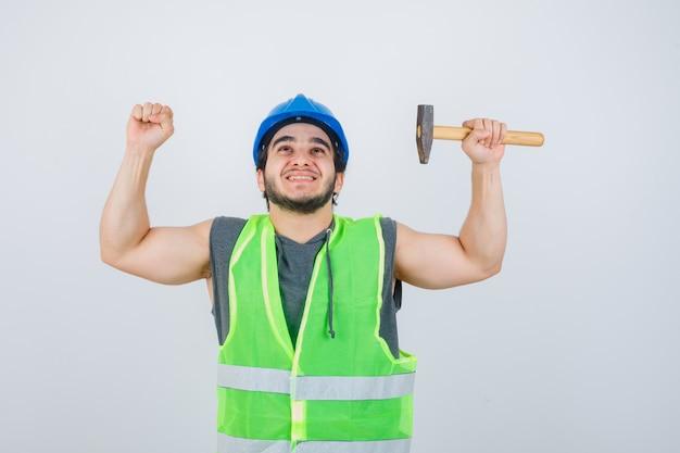 Junger baumeistermann, der hammer hält, während siegergeste in arbeitskleidunguniform zeigt und glück schaut. vorderansicht.