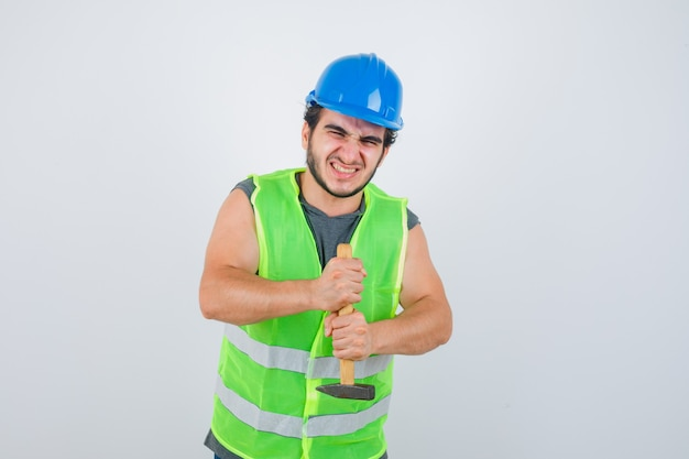Junger baumeistermann, der hammer in arbeitskleidunguniform hält und stärker schaut. vorderansicht.