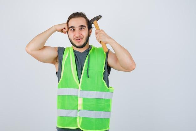 Junger baumeistermann, der hammer und faust auf kopf in arbeitskleidunguniform hält und freudig, vorderansicht schaut.
