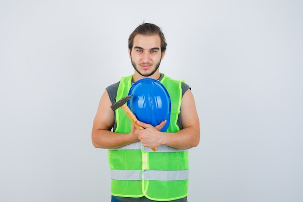Junger baumeistermann, der hammer und helm auf brust in arbeitskleidunguniform hält und erfreut schaut. vorderansicht.