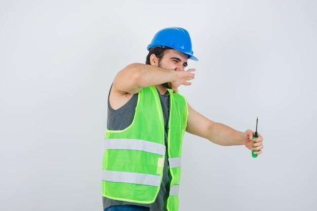 Junger baumeistermann, der hand auf mund hält, während schraubendreher in uniform hält und glückliche vorderansicht schaut.