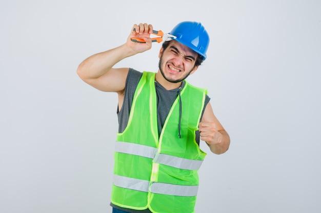 Junger baumeistermann, der helm mit zange kneift, während geballte faust in arbeitsuniform zeigt und amüsiert aussieht. vorderansicht.