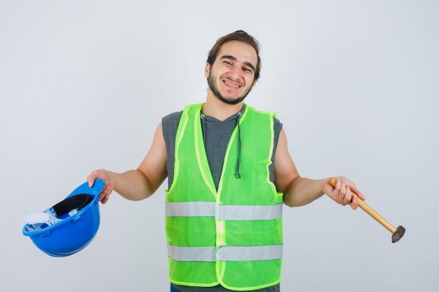Junger baumeistermann, der helm und hammer in arbeitskleidunguniform hält und fröhlich, vorderansicht schaut.