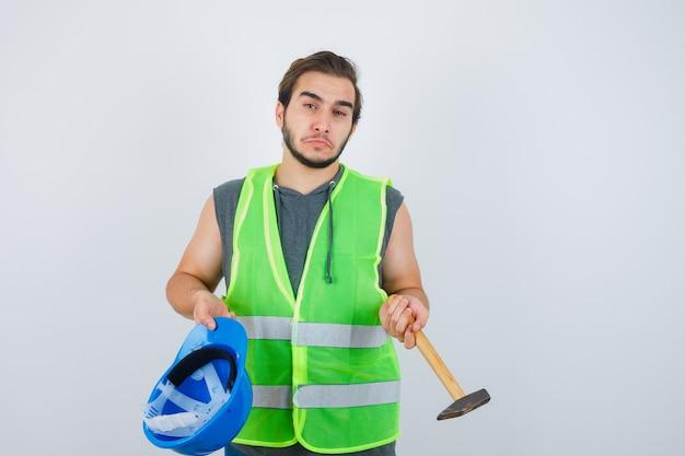 Junger baumeistermann, der helm und hammer in arbeitskleidunguniform hält und indikativ aussieht. vorderansicht.