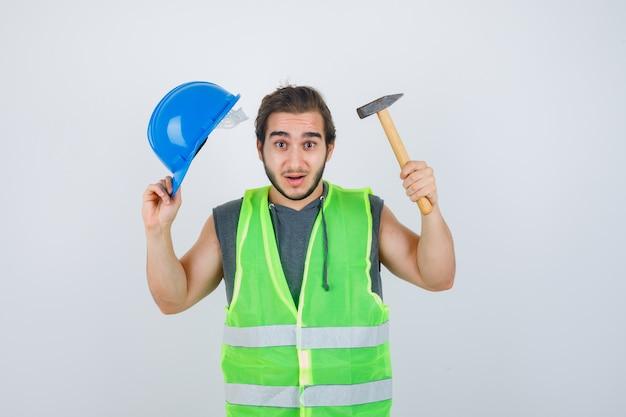 Junger baumeistermann, der helm und hammer in arbeitskleidunguniform hält und ratlos, vorderansicht schaut.