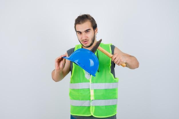 Junger baumeistermann, der helm und hammer in arbeitskleidunguniform hält und zuversichtlich schaut. vorderansicht.