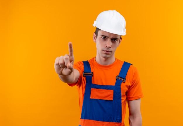 Junger baumeistermann, der konstruktionsuniform und sicherheitshelm trägt, der finger oben tut