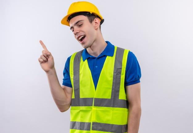 Junger baumeistermann, der konstruktionsuniform und sicherheitshelm trägt, tanzt mit finger