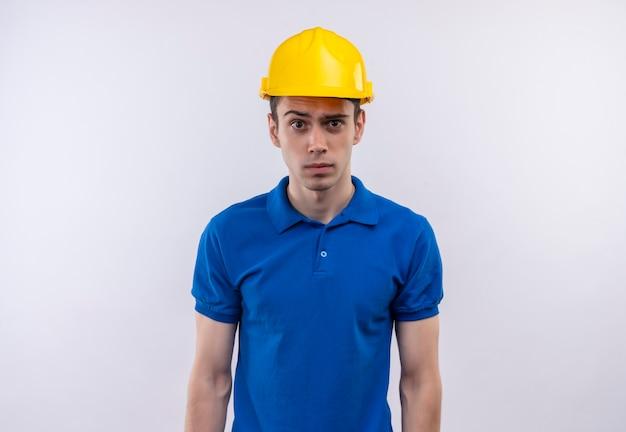 Junger baumeistermann, der konstruktionsuniform und sicherheitshelm trägt, überraschtes gesicht tut