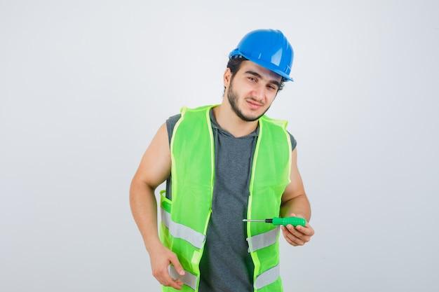 Junger baumeistermann, der schraubendreher hält, während in uniform wegschaut und selbstbewusst, vorderansicht schaut.