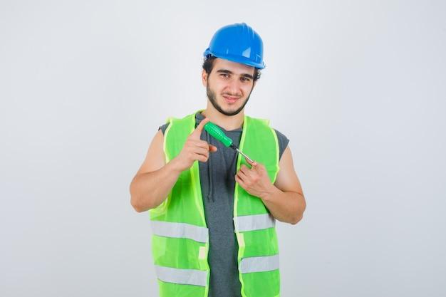 Junger baumeistermann, der schraubendreher in uniform hält und selbstbewusst, vorderansicht schaut.