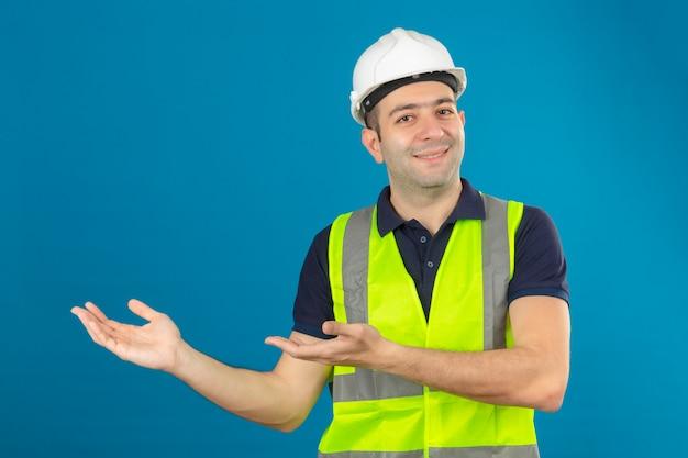 Junger baumeistermann, der weißen helm und eine gelbe weste trägt, mit einem lächeln auf gesicht, das mit handfläche auf kopienraum auf blau lokalisiert zeigt