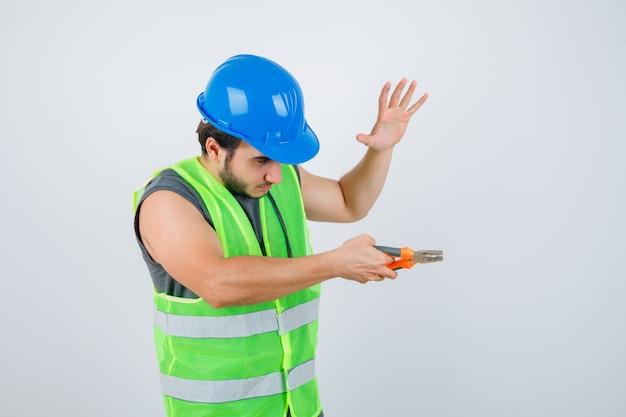 Junger baumeistermann, der zangen hält, während handfläche in arbeitskleidunguniform angehoben wird und selbstbewusst aussieht. vorderansicht.