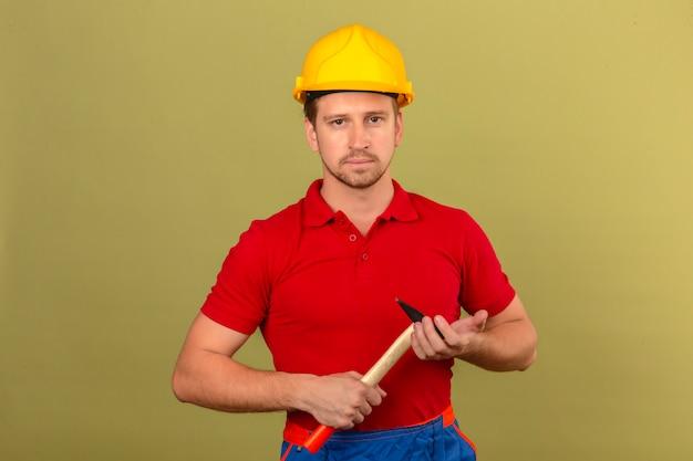 Junger baumeistermann im roten poloshirt und im sicherheitshelm, der hammer mit ernstem gesicht über isolierter grüner wand hält