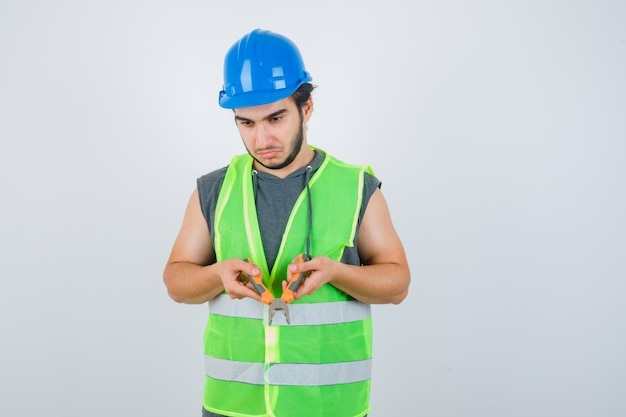 Junger baumeistermann in arbeitskleidunguniform, die zangen hält und nachdenklich, vorderansicht schaut.