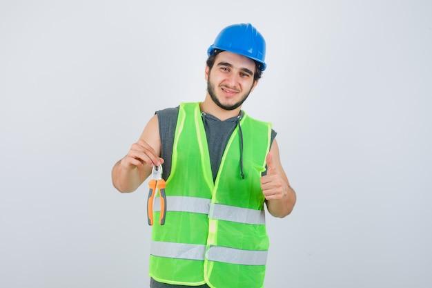 Junger baumeistermann in arbeitskleidunguniform, die zangen hält, während daumen oben zeigt und erfreut, vorderansicht schaut.