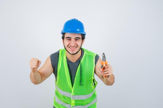 Junger baumeistermann in arbeitskleidunguniform, die zangen hält, während siegergeste zeigt und glückliche vorderansicht schaut.