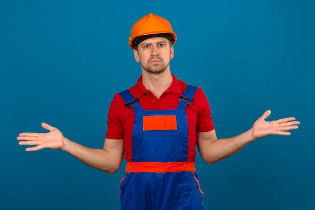 Junger baumeistermann in bauuniform und sicherheitshelm ahnungslos und verwirrter ausdruck mit armen und händen hob zweifel konzept über isolierte blaue wand auf