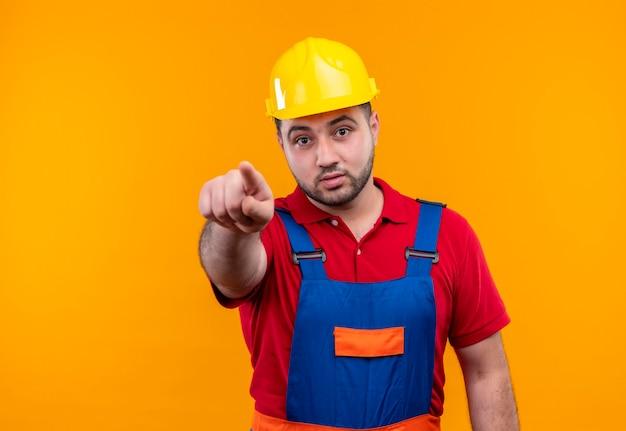 Junger baumeistermann in bauuniform und sicherheitshelm, der mit zeigefinger zur kamera zeigt, die überrascht schaut