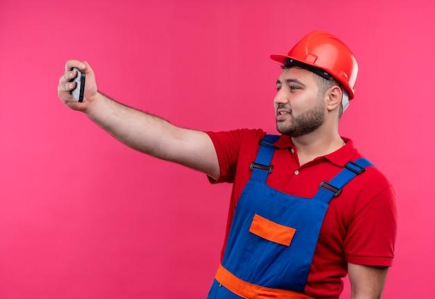 Junger baumeistermann in bauuniform und sicherheitshelm, der selfie unter verwendung seines handys lächelnd macht
