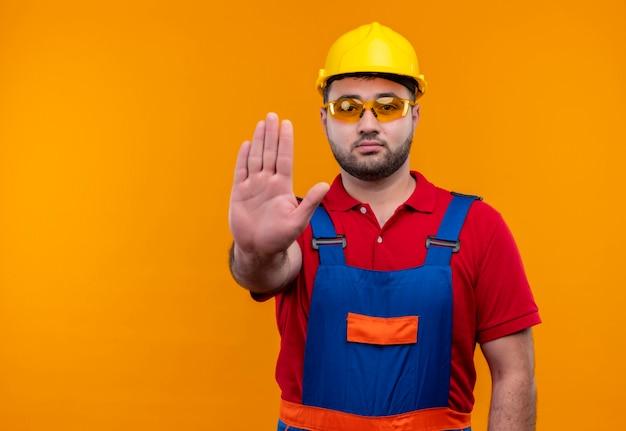 Junger baumeistermann in bauuniform und sicherheitshelm mit offener hand, die stoppschild mit ernstem gesicht macht