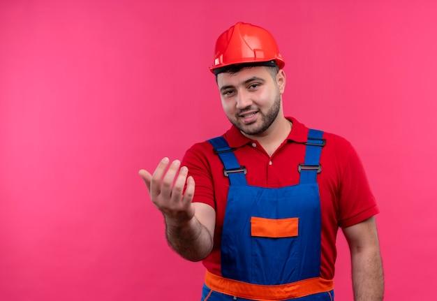 Junger baumeistermann in bauuniform und sicherheitshelmherstellung kommen hier geste mit hand lächelnd freundlich