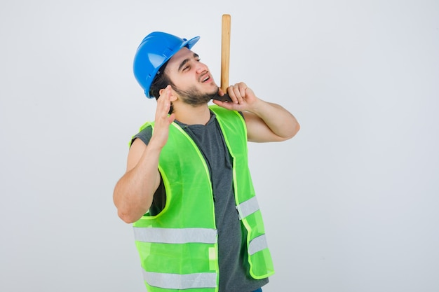Junger baumeistermann in der arbeitskleidunguniform, die hammer hält, während hand hebt und fröhlich, vorderansicht schaut.